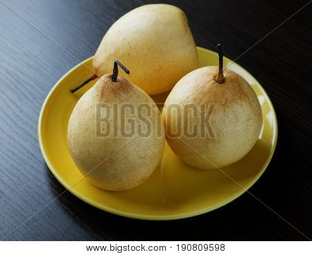 Three Yellow Pears On The Plate On The Table