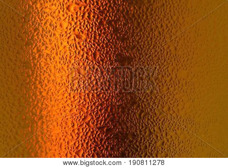 Macro shot of water droplets on orange gold colored bottle, for abstract background with selective focus