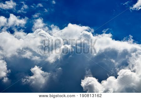 Blue sky with white and gray cumulus clouds. Closeup