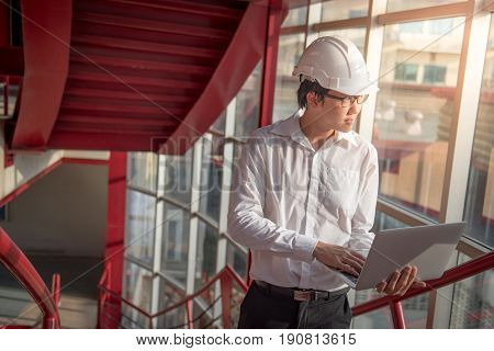 Young Asian Engineer or Architect working with laptop computer while wearing a personal protective equipment safety helmet at construction site. Engineering and building construction concepts