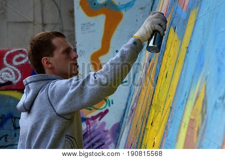 A Young Red-haired Graffiti Artist Paints A New Graffiti On The Wall. Photo Of The Process Of Drawin