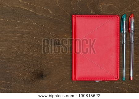 Red notebook and Colored gel pens on wooden background