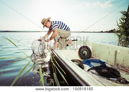 Fisherman at work, cleaning the nets on the boat