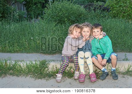 Portrait of three small joyful children sitting on the curb and embracing