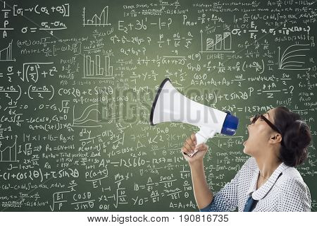 Businesswoman shouting through megaphone against green chalkboard with mathematical formula