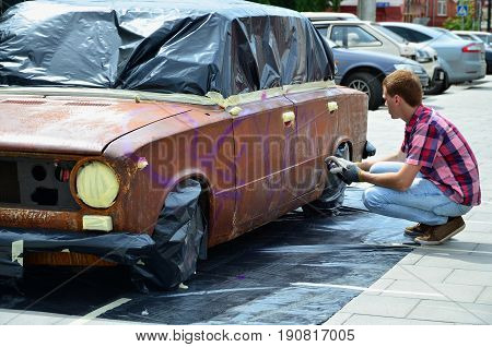 A Young Red-haired Graffiti Artist Paints A New Colorful Graffiti On The Car. Photo Of The Process O