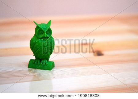 The model printed on a 3d printer. Object in the form of an owl of green color is on the table. Progressive modern additive technology. Copy spase, spase for text.