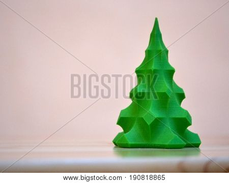 The model printed on a 3d printer. A small green tree is on the table. Progressive modern additive technology. Copy spase, spase for text.