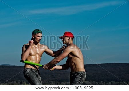 macho men or muscular athletes with naked strong torsos in green and red caps and jeans fighting with baseball bat on blue sky on mountain landscape. Conflict and competition. Power success