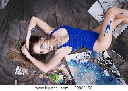 Young female artist painting abstract picture in studio beautiful sexy woman portrait toned image