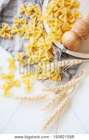 raw farfalle pasta with vegetables on white