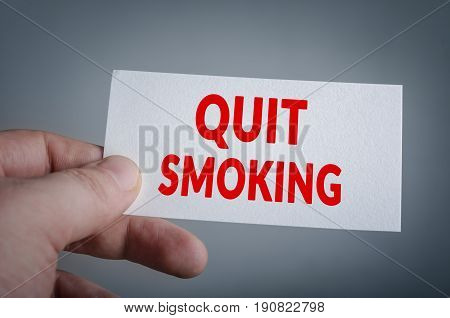 Quit smoking card in hand with dark background