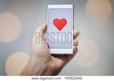 Hand holding smart phone with sending word and heart shape on screen with bokeh lights background. Happy Valentine's day!
