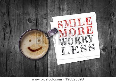 Smile more worry less inspirational quote on paper note with coffee cup top view.