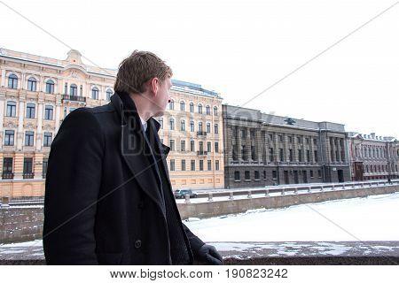 Man In A Black Coat On The Bridge In Winter