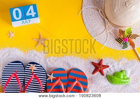 July 4th. Image of july 4 calendar with summer beach accessories and traveler outfit on background. Summer Vacation concept.