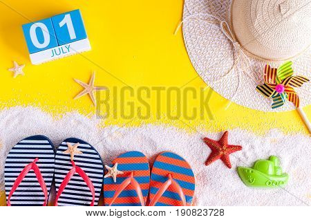 July 1st. Image of july 1 calendar with summer beach accessories and traveler outfit on background. Summer vacation concept.