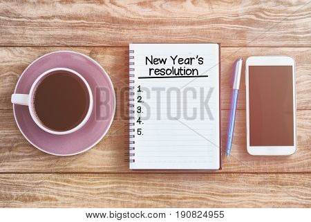 New Year's Resolution List On Note Pad, Wood Table With Coffee, Pen And Smart Phone Retro Styled.