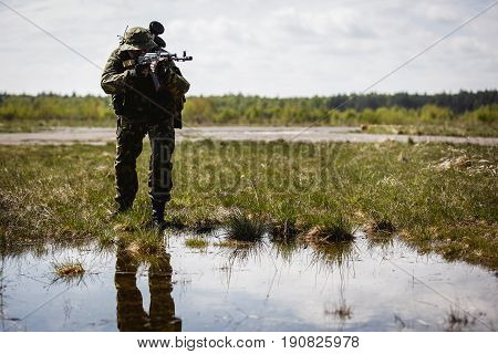 Photo of military man with gun in field during day