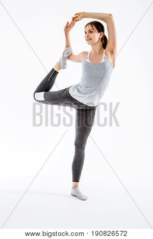 Athlete stretching on one leg at isolated background