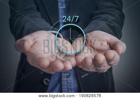 Businessman hand with symbol of on worldwide 24/7 service. Worldwide nonstop (full time 24/7) service concept.