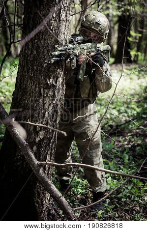 Soldier with arms behind tree in woods