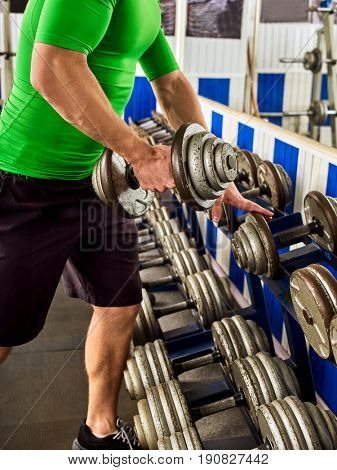 Man in gym workout with fitness equipment. Man holding dumbbell workout at gym. Stand with chrome dumbbells next to mirror. Selecting suitable weight dumbbell.