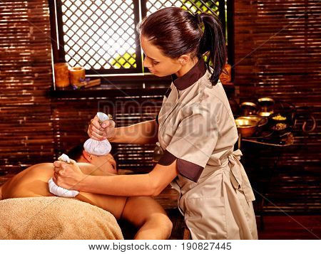 Man having Ayurveda massage with herbal hot ball. Therapy in Indian curative salon. Luxary bamboo interior in oriental therapy room. Group candels background.