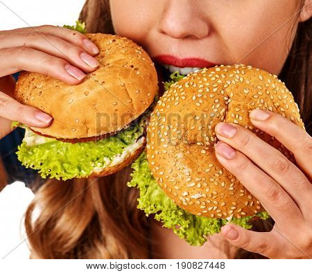 Woman eating french fries and hamburger. Portrait of student consume fast food on table. Girl trying to eat junk. Cropped shot of girl is suffering from gluttony.