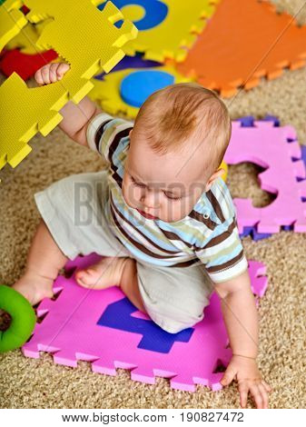 Child jigsaw develops children. Family puzzle making baby. Portrait of boy top view. Playing on floor in kindergarten. Kid learns to count and study of figures when playing.