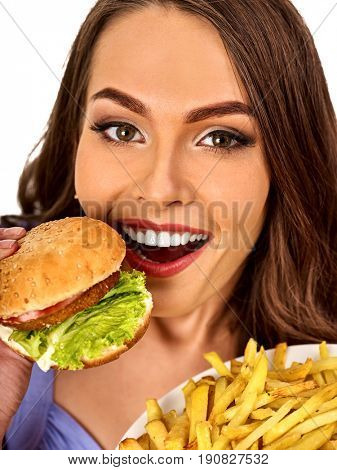 Woman eating french fries and hamburger. Portrait of student consume fast food on table. Girl trying to eat junk. Girl is having supper after hard day's work. Person broke off from diet.