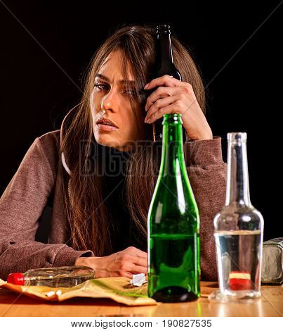 Woman alcoholism is social problem. Female drinking is cause of poor health. She drinking alcohol in bad mood. Table with empty bottle. Morning after student's party on black background.