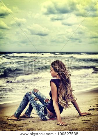 Summer girl sea. Woman sitting on coast near ocean with waves. Girl dressed in torn jeans dreams of love. Green sky and clouds with backlit on background. Shiny tone background.