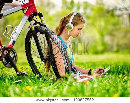 Bikes cycling girl. Girl rides bicycle. Girl wearing headset in cycling watch in pc tablet near bicycle. Cyclist looking pc tablet and listing music . Woman in social network communicates with friends