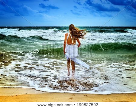 Summer girl sea. Woman goes at water on coast. Girl came out of sea foam. Female with long hair in white sundress walking barefoot on seawater beach. Blue sky and green wave of sea with wind. Outdoor.