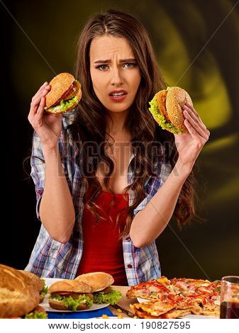 Upset girl holding big two small hamburgers and pizza. Fastfood concept on green background. Female is sad about failure of diet.