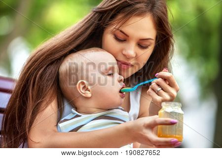 Baby feeding spoon by mother in park outdoor. Weaning in first weeks. Portrait of happy beautiful mom and eating child summer on bench. Good appetite fresh air by baby food.