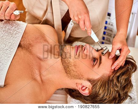 Facial massage at beauty salon. Electric stimulation skin care of man. Equipment for microcurrent lift face. Anti aging face and neck rejuvenation non surgical treatment indoor. Improvement of skin.