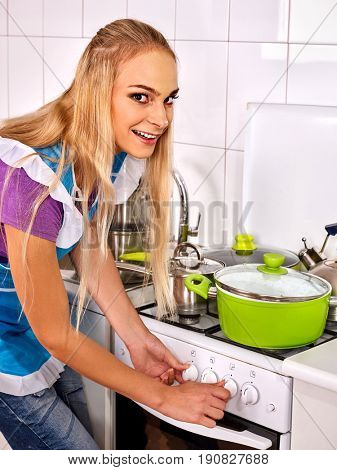 Preparing vegetarian meal home kitchen. Woman in blue apron cook soup by woman in meal of vegetables . Interior is light style. Preparation of home dinner. Green saucepan on an electric stove.
