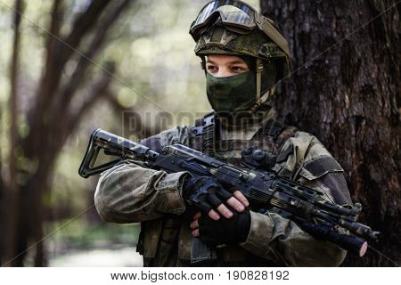 Portrait of soldier with submachine gun standing in woods during day