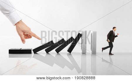 Man running from falling huge dominoes while male hand pushing them on light background. Concept of irresponsible business strategy