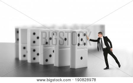 Man pushing huge dominoes on table. Concept of irresponsible business strategy