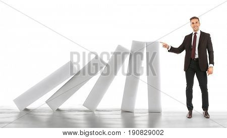 Man trying to stop falling huge dominoes on white background. Leadership concept