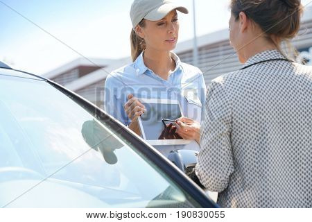 Woman in parking lot renting car from rental company