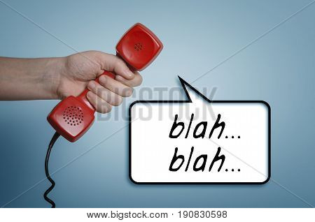 Blah..blah..blah..Hand with old red telephone handset receiver and speech bubble.