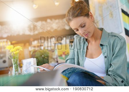 Woman in lounge reading magazine at lunch time
