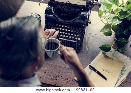 Man drinking coffee with vintage typewriter