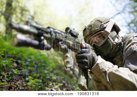Portrait of soldier with submachine gun on military mission in forest