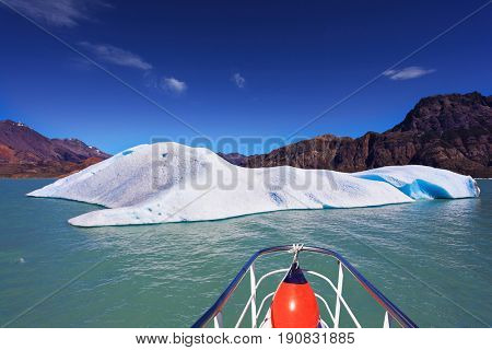 Ice and sun Patagonia. White-blue huge icebergs float near a ship board. Excursion on the tourist boat on Lake Viedma