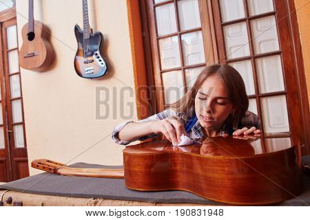 Woman as trainee cleaning guitar in guitar maker workshop
